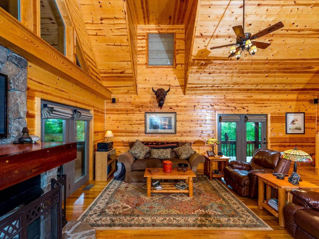 Image de Grande salle avec plafond cathédrale et portes françaises ouvrant sur le pont à 733 Bolens Creek Rd, Burnsville, une cabine de montagne NC à vendre.